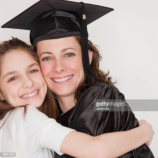 daughter (10-11 years) embracing mother after her graduation, smiling, portrait - 30 34 years stock-fotos und bilder
