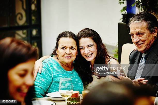 Daughter embracing mother for photo during party