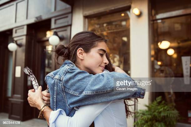 daughter embracing mother while standing by shops in city - black and white instant print stock pictures, royalty-free photos & images
