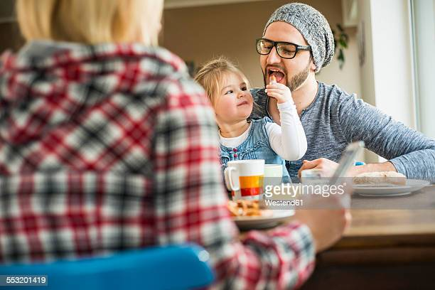 Daughter feeding father at dining table