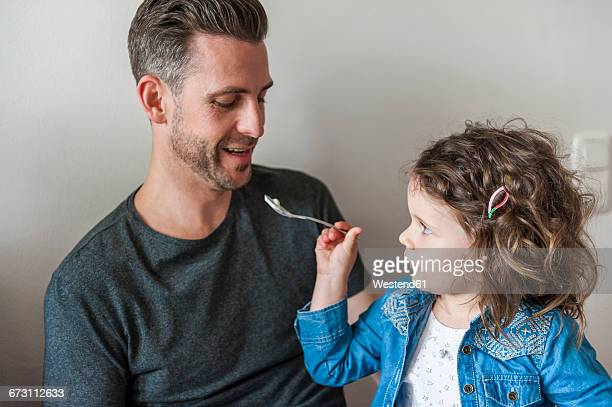 Daughter feeding father