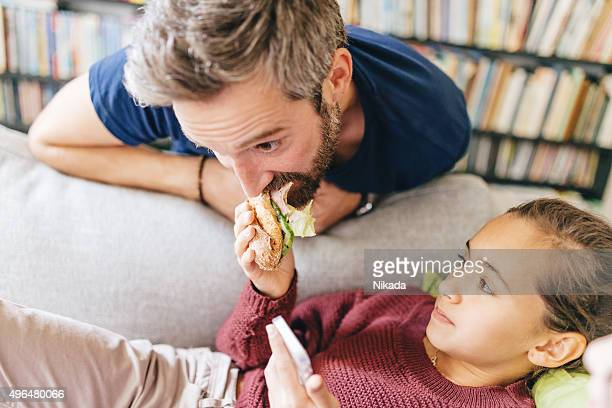daughter feeding father with sandwich
