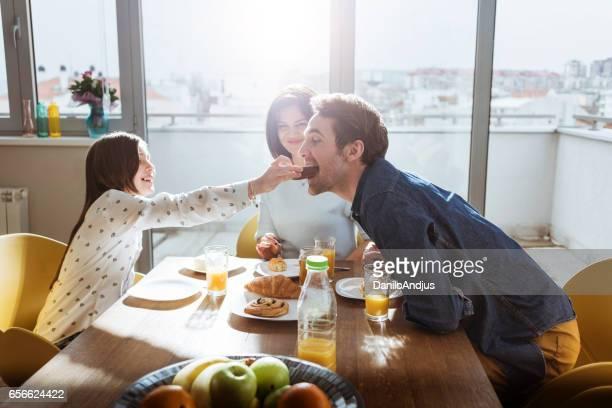 Tochter, füttern ihrem Vater beim Frühstück