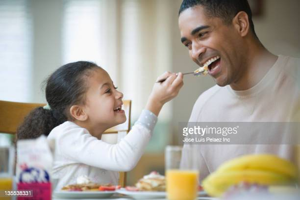 Daughter feeding pancakes to father
