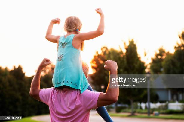 daughter flexing muscles with father - flexing muscles stock pictures, royalty-free photos & images
