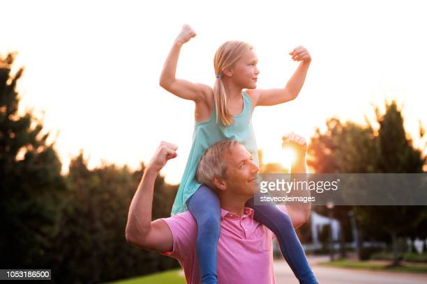 Daughter Flexing Muscles with Father