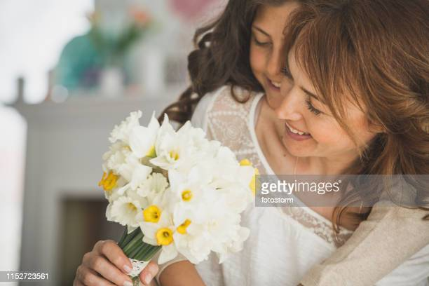 daughter gifting daffodils to her mother - tulips and daffodils stock pictures, royalty-free photos & images