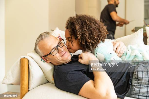 daughter gives a kiss to her dad on couch - domenica foto e immagini stock