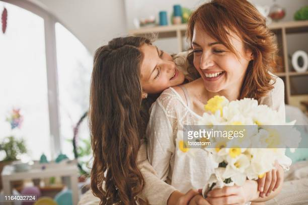 daughter giving flowers to her mother at home - mothers day stock pictures, royalty-free photos & images