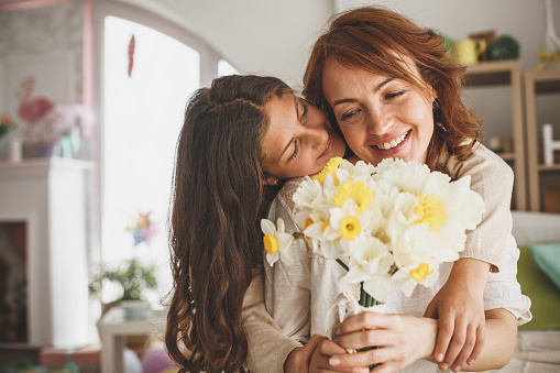 Daughter giving flowers to her mother at home 1169246392