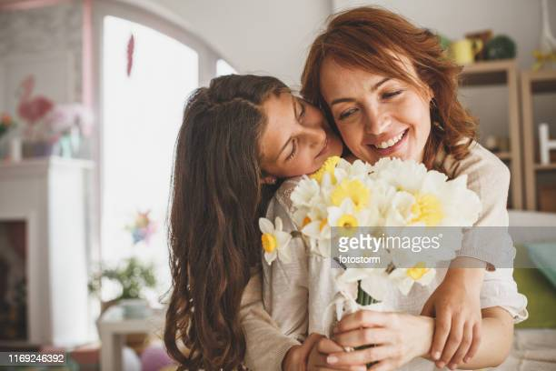 daughter giving flowers to her mother at home - mother's day stock pictures, royalty-free photos & images
