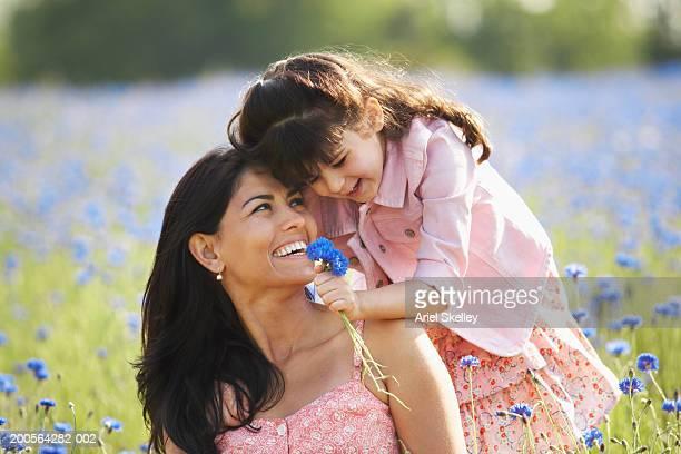 daughter (4-5) giving flowers to mother in flower field - muttertag blumen stock-fotos und bilder
