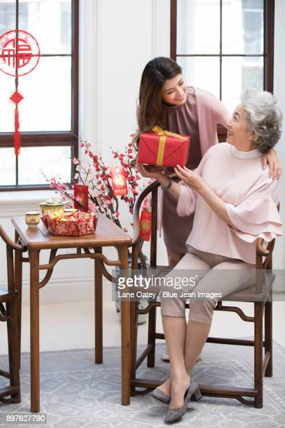 Daughter giving gift to her mother during Chinese New Year