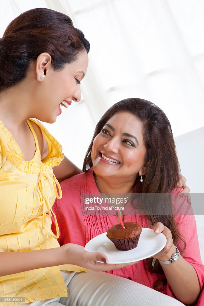 Daughter giving mother a cupcake : Stock Photo