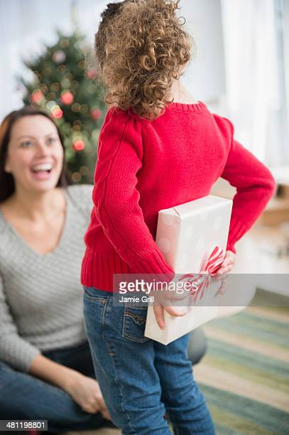 Daughter giving present to Mom at Christmas