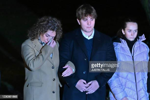Daughter Hannah Ingram-Moore wipes a tear from her eye as she waits with her children Benjie and Georgia outside their residence before taking part...