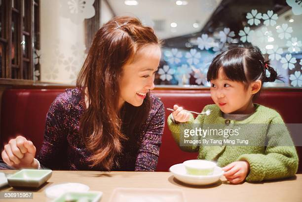 Daughter having dessert with mom in restaurant