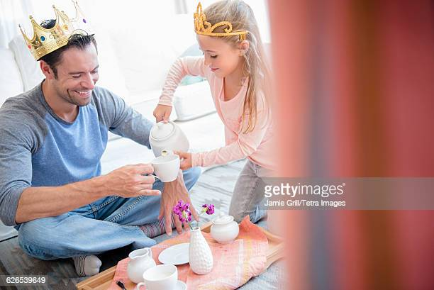 daughter (6-7) having tea party with father - tea party stock pictures, royalty-free photos & images