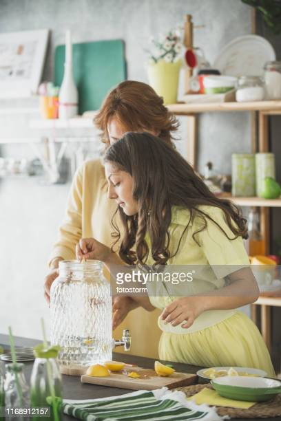 daughter helping her mother prepare lemonade - mint plant family stock pictures, royalty-free photos & images