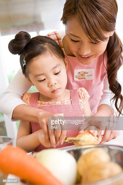 Daughter helping mother cook