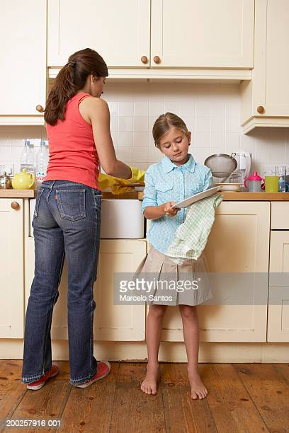 daughter (3-5) helping mother dry dishes in kitchen - kids with cleaning rubber gloves stock pictures, royalty-free photos & images