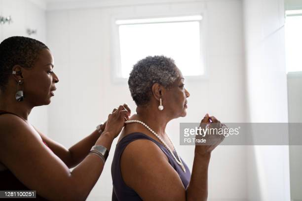 daughter helping mother fastening pearl necklace - pearl necklace stock pictures, royalty-free photos & images
