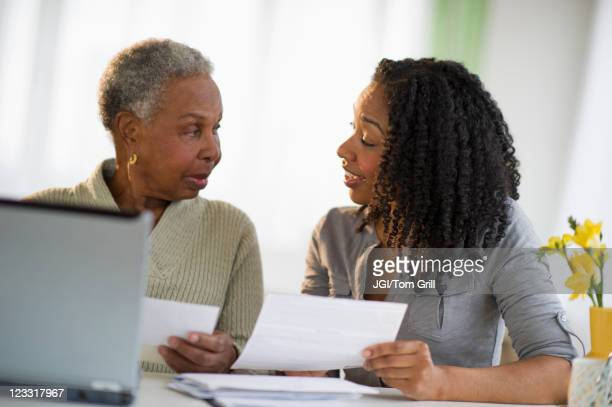 Daughter helping mother pay bills online