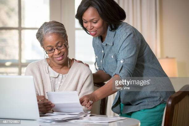 Daughter helping mother pay bills