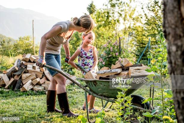 Daughter Helping Mother To Stacking Firewood In The Mountain House