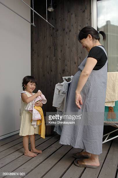 Daughter (4-6) helping pregnant mother with laundry
