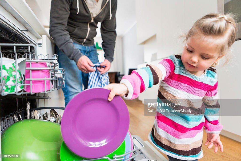 Daughter helping to stack dishwasher : Stock Photo