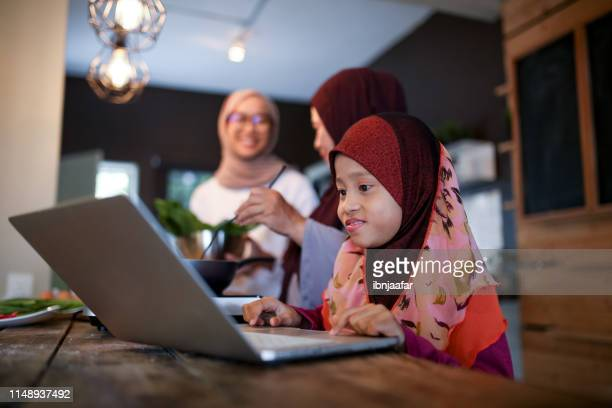 daughter helps mother in kitchen while looking to laptop - eid al adha stock pictures, royalty-free photos & images