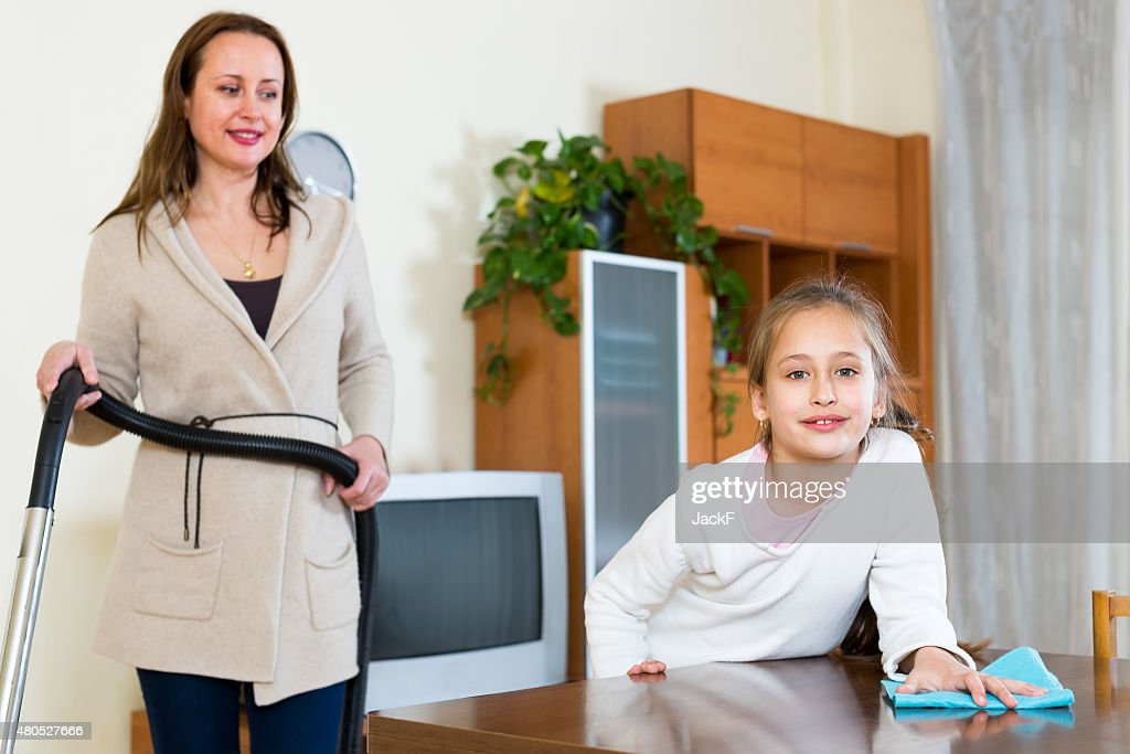 Daughter helps mother with cleaning : Stockfoto