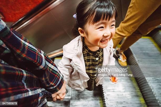 Daughter holding dad's hand on escalator