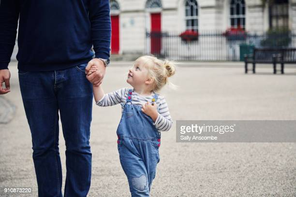Daughter holding fathers hand