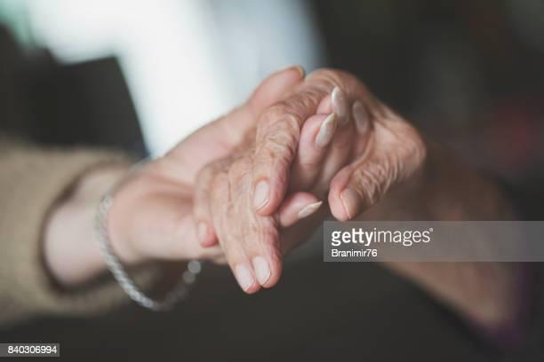 Fille, tenant la main de sa vieille mère