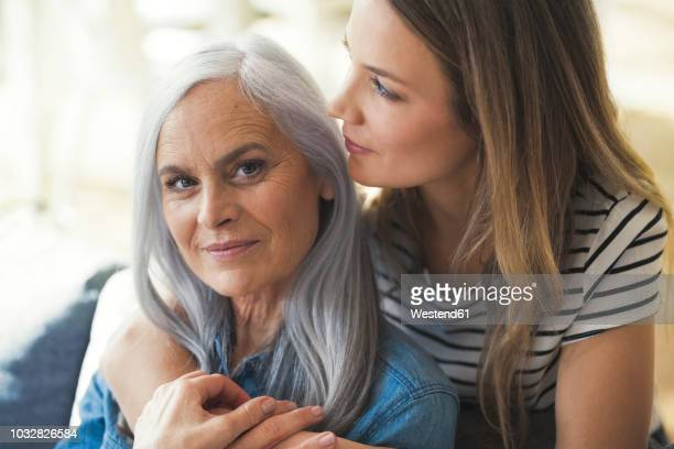 daughter holding mother in her arms - seulement des adultes photos et images de collection