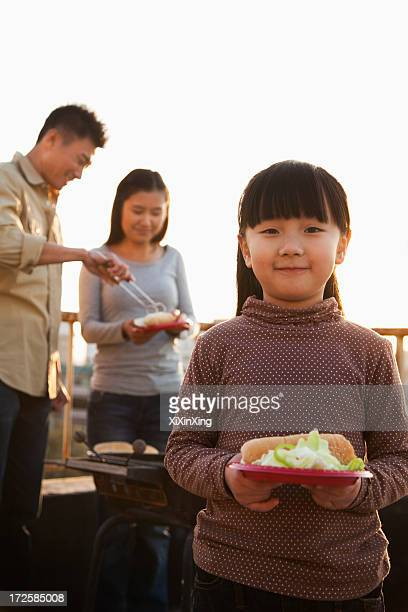 daughter holding plate with hotdog and salad, parents standing next to the barbeque - östasiatiskt ursprung bildbanksfoton och bilder