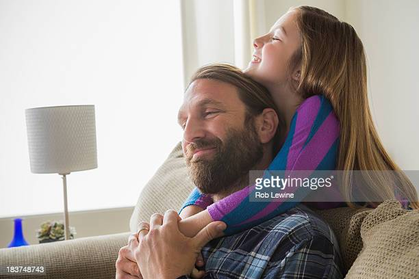 Daughter hugging father from behind sofa