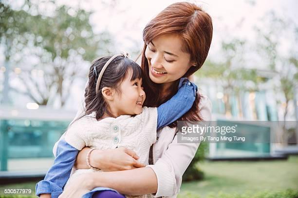 Daughter hugging her mom joyfully in park