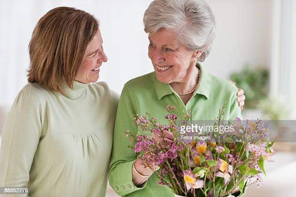 Daughter hugging mother holding flowers
