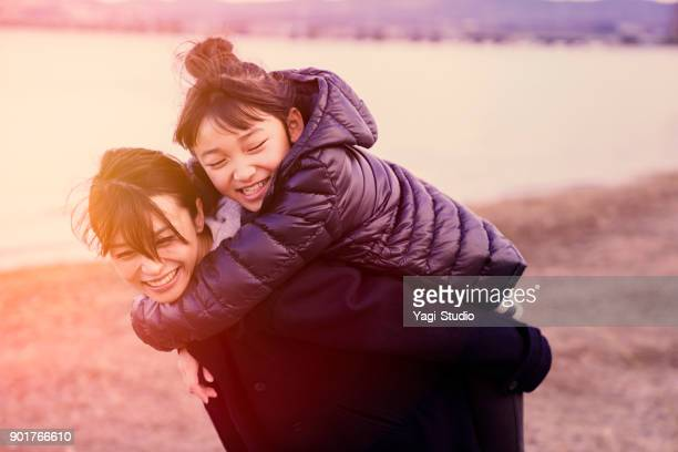 Daughter hugging mother near the lake in winter