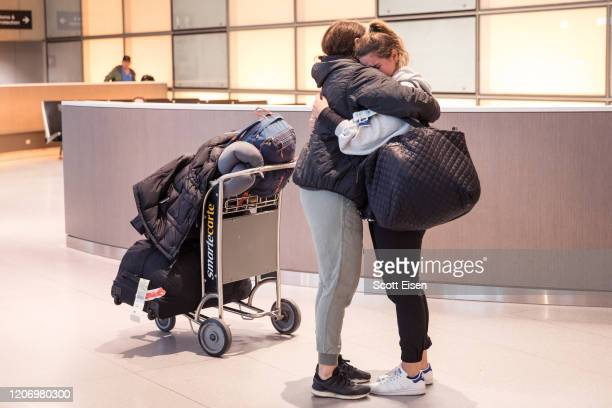 Daughter hugs her mother after arriving on an international flight at Logan Airport on March 13, 2020 in Boston, Massachusetts. The Trump...