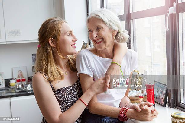 daughter hugs mother in kitchen - daughter stock pictures, royalty-free photos & images