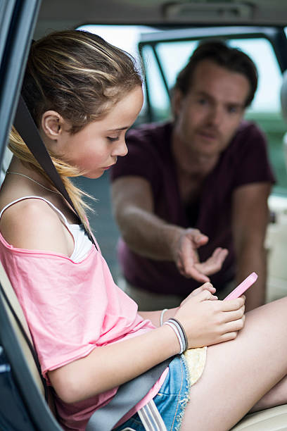 daughter ignoring father while using mobile phone in car - parent ignoring child stock pictures, royalty-free photos & images