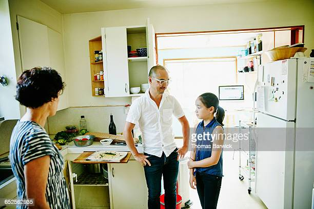 Daughter in discussion with parents in kitchen