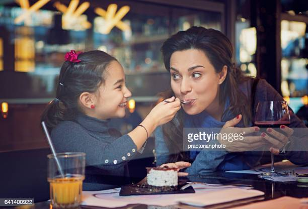 Daughter is feeding her mother with cake