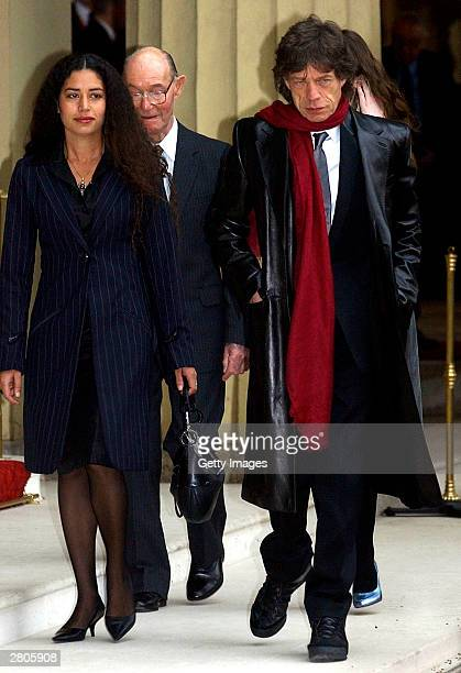 Daughter Karis with her father veteran rocker Sir Mick Jagger of the Rolling Stones leave Buckingham Palace on December 12 2003 in London Jagger...
