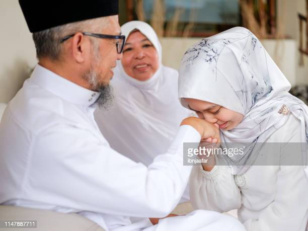 daughter kiss father hand - eid al adha stock pictures, royalty-free photos & images