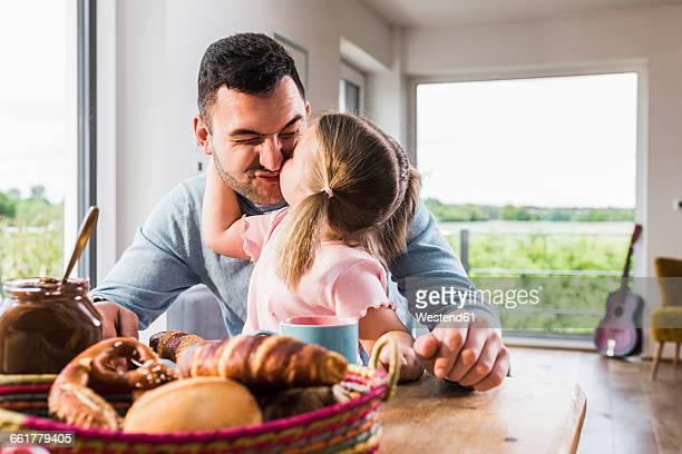 Daughter kissing father at breakfast table